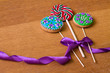 Gingerbread with flowers and lollipop with purple bow on table.