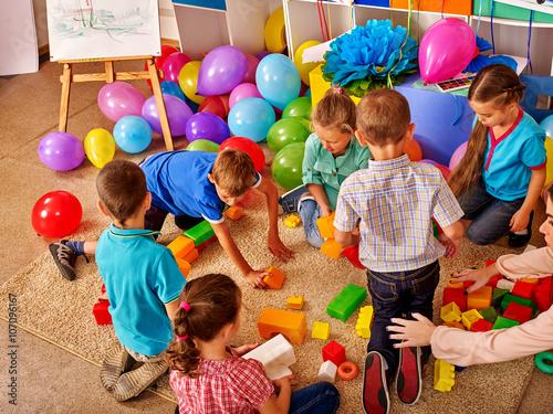 Fototapeta Group children game blocks on floor in kindergarten Balloons on floor Top view