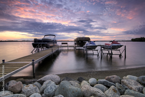 Cuadros en Lienzo Boat dock at sunset with raised boats and jet ski's