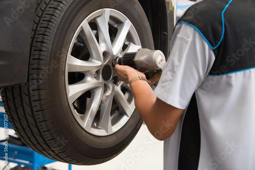 Zdjęcie XXL Mechanik pracuje na samochodowym koła zaciśnięciu lub rozluźnieniu rygiel