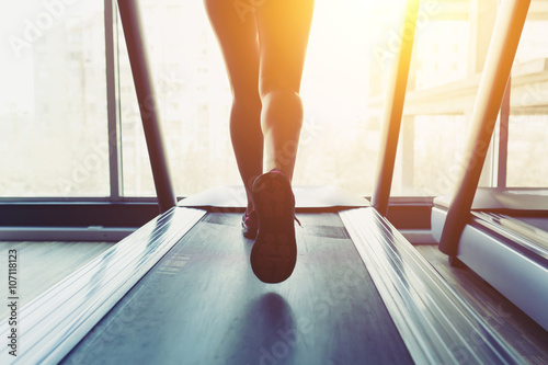 Fototapeta Fitness girl running on treadmill