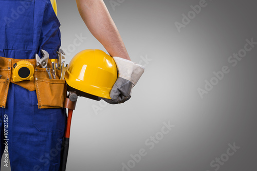 construction worker holding helmet on gray background with copy