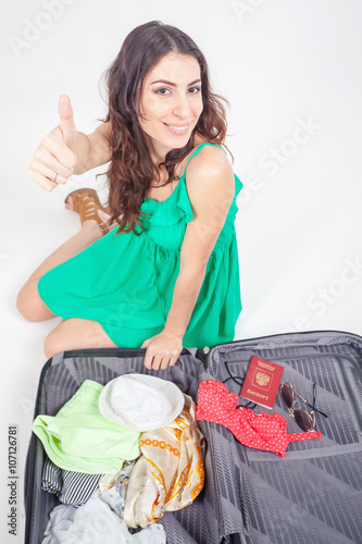 Photo  Young woman packs her things, clothes at luggage