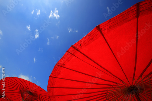 Noerthern Thailand traditional red parasols with clear blue sky