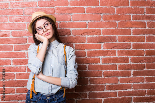 Fotografia, Obraz  Beautiful young dark-haired girl in casual clothes posing and bored, standing ag