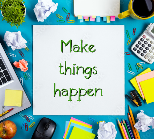 Make things happen. Office table desk with supplies, white blank note pad, cup, pen, pc, crumpled paper, flower on blue background. Top view © projectio