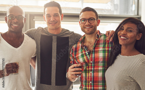 Four smiling adult friends in office
