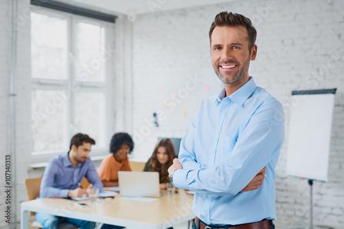Fotografía  Feliz hombre de negocios de pie en la oficina con sus compañeros de trabajo en e