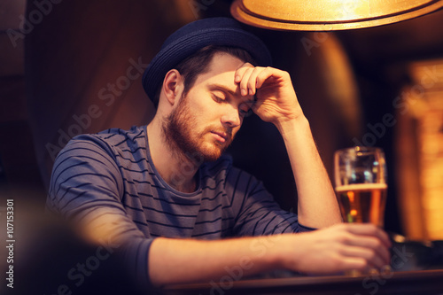 Fotografía  unhappy lonely man drinking beer at bar or pub