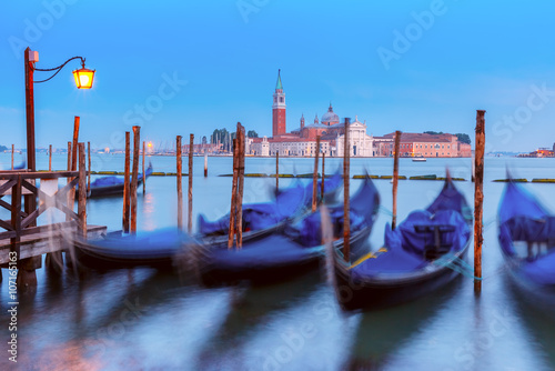 Staande foto Gondolas Gondolas moored by Saint Mark square with San Giorgio di Maggiore church in the background in the evening, Venice, Italia