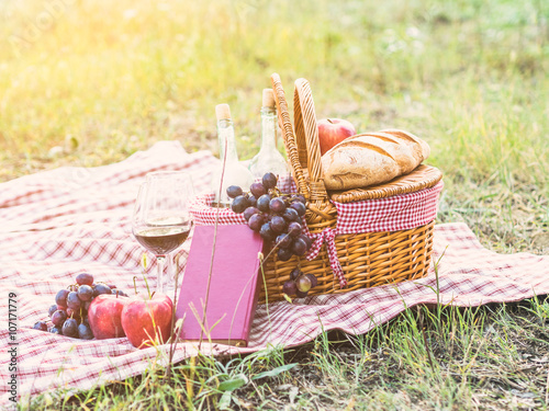 Poster Picnic In a field a couple has placed a towel with a picnic basket. Around there are bottles of wine with glasses, fruit, bread and a book
