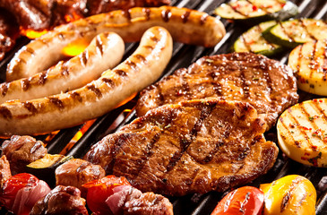 FototapetaVarious meats and vegetables on hot grill