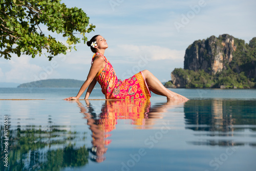 Woman in traditional thai summer dress enjoying travel and relax in Krabi, Thailand. Beautiful girl relaxing at poolside towards the sea during asian travel.