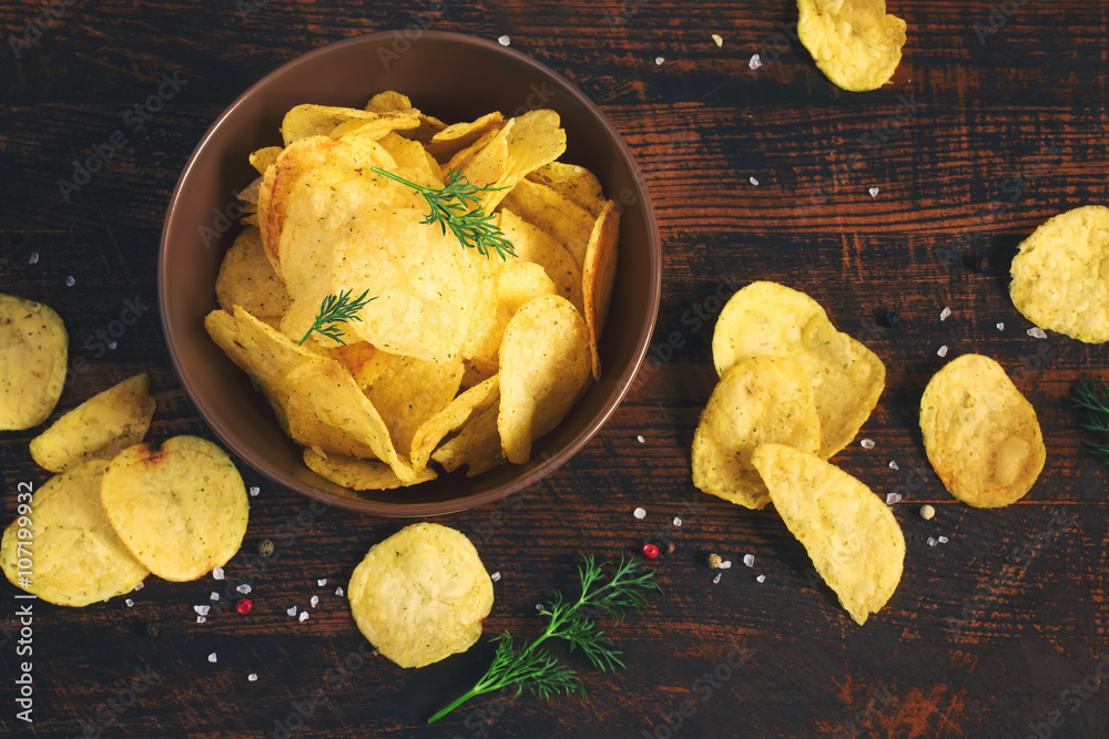 Fototapeta Crispy potato chips in a cup on a dark background, tinted