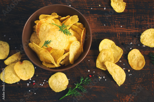Valokuva  Crispy potato chips in a cup on a dark background, tinted