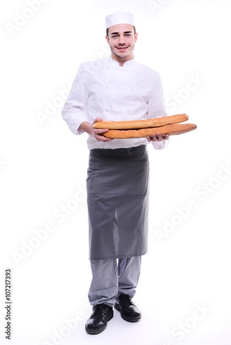 Fotografie, Obraz  young baker isolated on white studio background holding a traditional bread fren