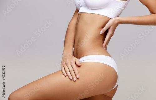 Fotografia Slim tanned woman's body over gray background