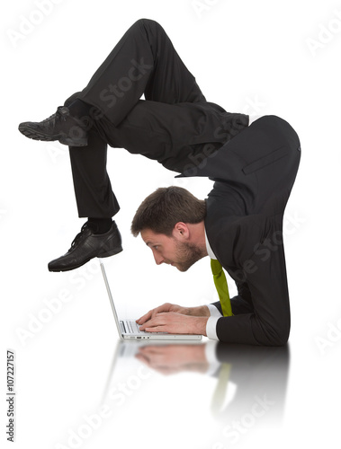Fotografie, Obraz  businessman work contortion with laptop isolated on white