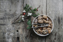 A Dish Of Nuts And A Nut Cracker On A Table With A Sprig Of Yew Wit Red Berries.