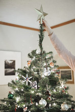 A Person Decorating A Christmas Tree At Home.