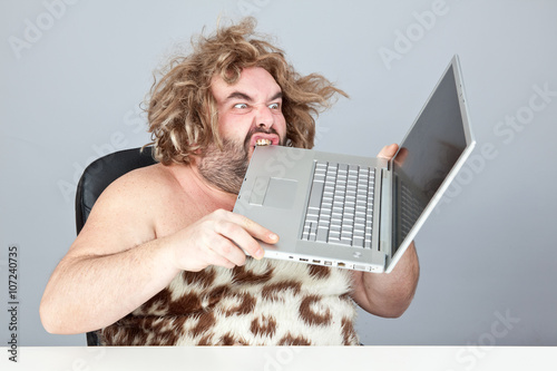 Photo  hungry and angry prehistoric man eat laptop
