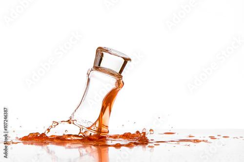 Fotografie, Obraz  Bicchiere in caduta con liquido arancione su sfondo bianco