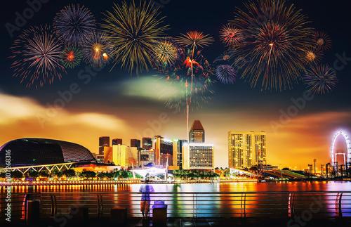 Poster Oceanië Multiple fireworks exploding high in the sky over modern buildin