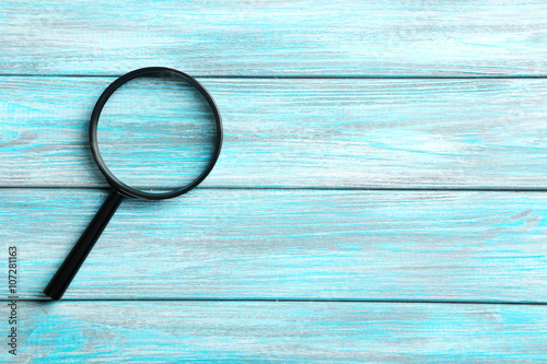 Fotografiet  Magnifying glass on a blue wooden table