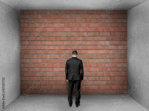 Businessman with bowed head stands front of a brick wall in interior Wallpaper Mural