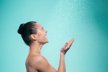 Woman Enjoying Water In The Shower Under A Jet