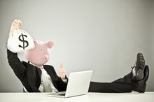 Funny Businessman With Pig Face Hold Money With Laptop On Grey Background