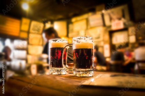 Photo Defocused bar blur with 2 mugs of beer in focus