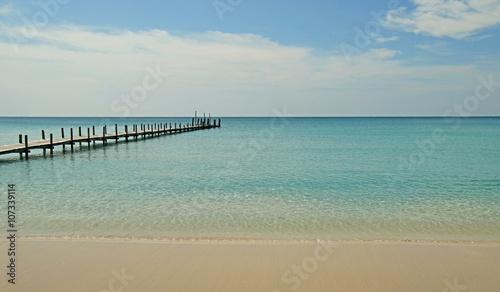 wooden jetty on sunny beach - 107339114
