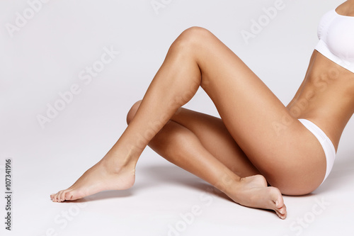 Obraz Slim tanned woman's body over gray background - fototapety do salonu