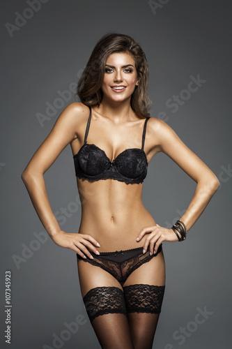Fotografie, Obraz  Beautiful happy lady in elegant black lace lingerie and stocking