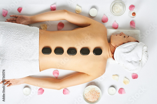 Woman having hot stones on her back in spa salon Poster