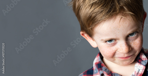 Foto closeup portrait of a young mischievous child with freckles teasing and grumblin