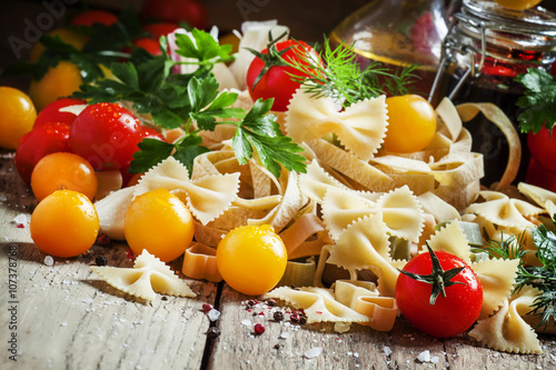 Tela  Italian food: Assorted dry pasta, herbs, garlic, red and yellow