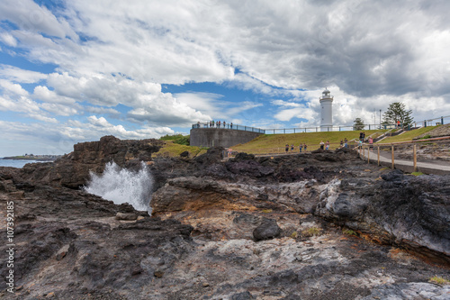 Fotografia, Obraz  Kiama Lighthouse with water spraying out of the blowhole, Sydney, NSW, Australia