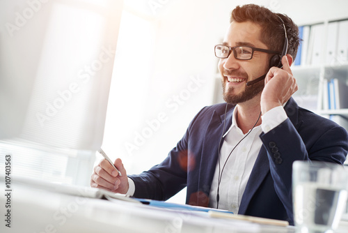 Smiling businessman using headset when talking to customer Obraz na płótnie