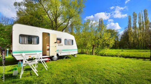 Caravan trailer on a green lawn, on a sunny spring day Canvas Print
