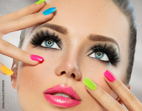 Cuadros en Lienzo Beauty girl face with colorful nail polish. Manicure and makeup