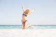Carefree woman in bikini jumping on the beach