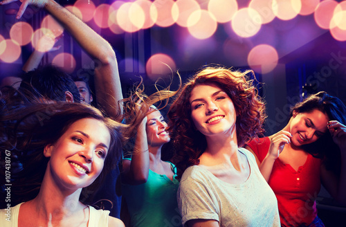 obraz lub plakat smiling friends dancing in club