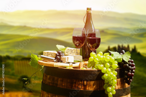 Photo sur Toile Vin Red wine bottle and wine glass on wodden barrel. Beautiful Tusca