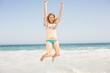 Carefree woman in bikini jumping on the beach