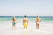 Rear view of young friends standing on the beach