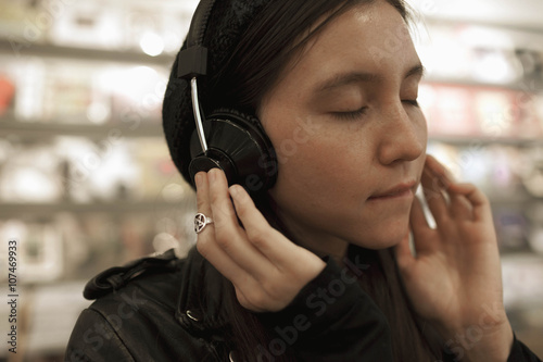 Spoed Foto op Canvas Muziekwinkel Young woman listening to music in a record store