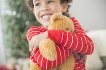 Mixed Race Boy Hugging Teddy Bear At Christmas