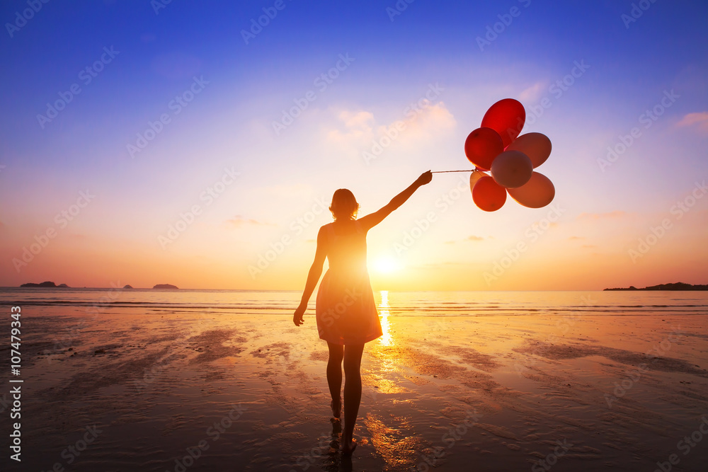 Fototapeta happiness concept, positive emotions, happy girl with multicolored balloons enjoying summer beach at sunset